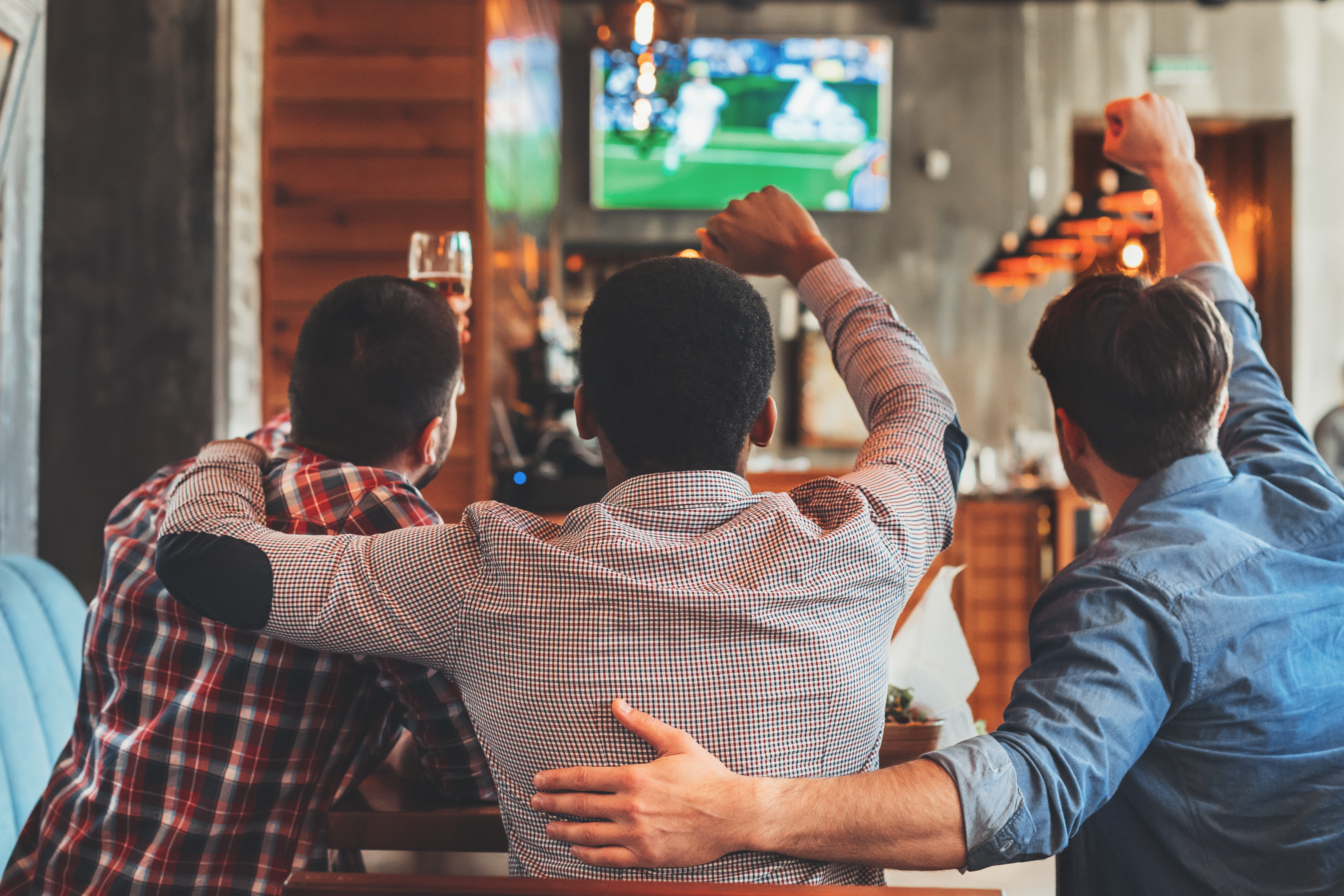 Three men watching football on TV in sport bar, back view